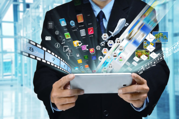 A businessman accesing internet and information technology via tablet / gadget in his hand