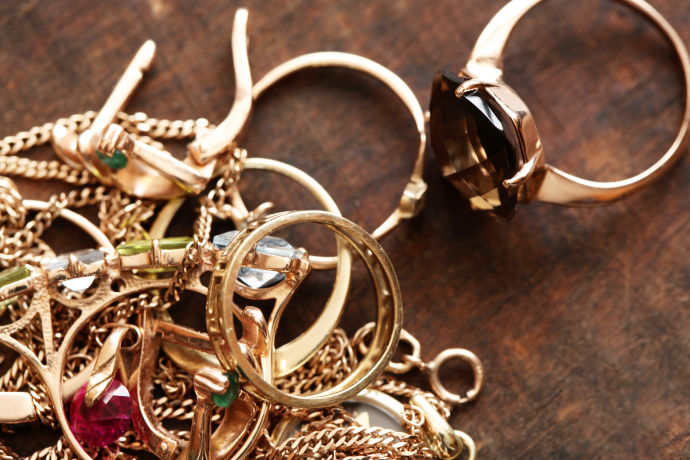 Closeup of pile of gold jewelry on wooden surface
