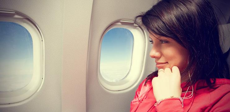 Девушка смотрит в окно самолета