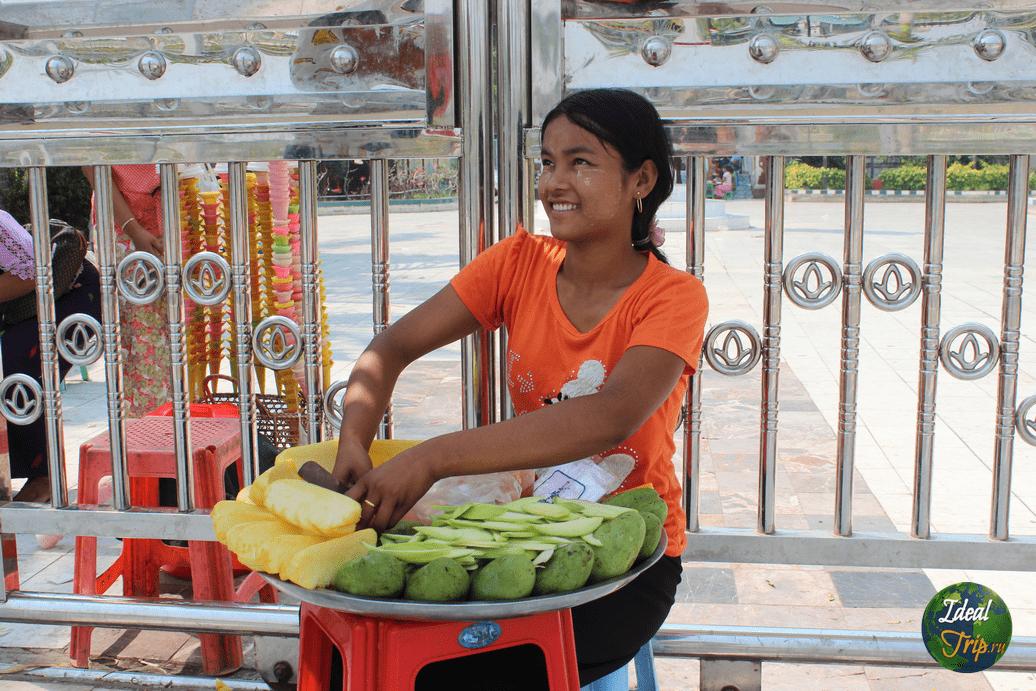 Девушка продает разрезанные Азиатские фрукты с красным перцем